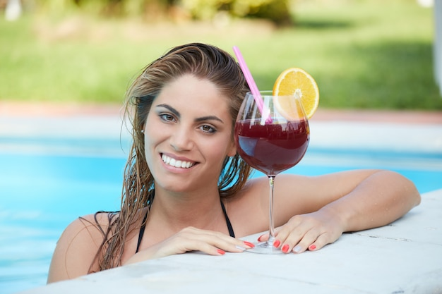 Donna che si distende e beve un cocktail in piscina