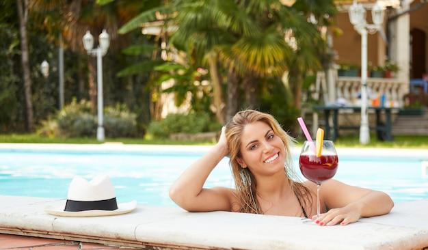 Donna che si distende e beve un cocktail in piscina