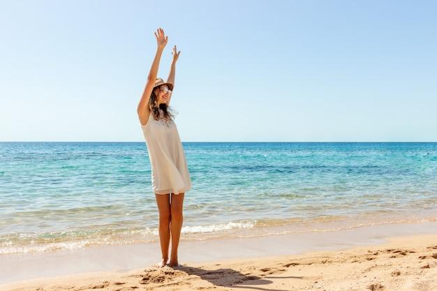 Donna che si distende in spiaggia godendo la libertà estiva. happ ragazza in spiaggia