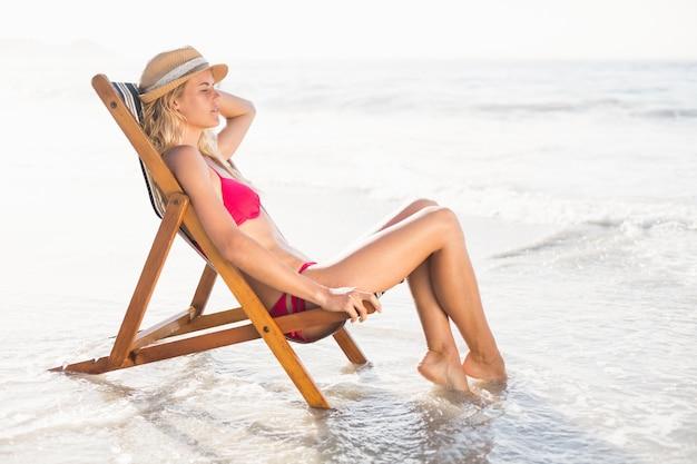Donna che si distende su una poltrona sulla spiaggia