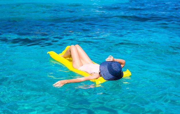 Donna che si distende sul materasso gonfiabile in mare limpido