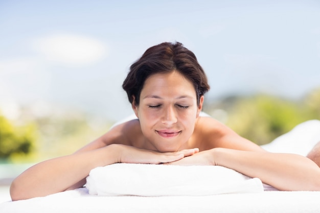 Donna che si distende sulla tabella di massaggio nella spa
