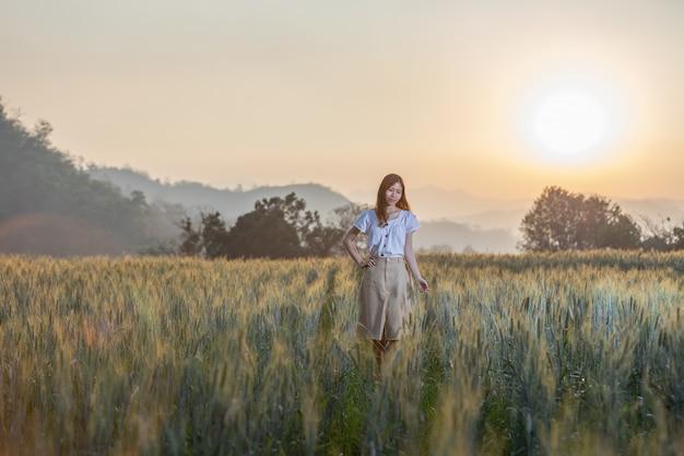 Donna che si diverte al campo di orzo al momento del tramonto