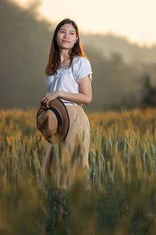 Donna che si diverte al campo di orzo in estate