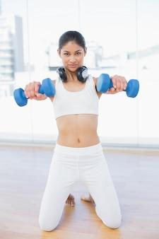 Donna che si esercita con i dumbbells nello studio di forma fisica
