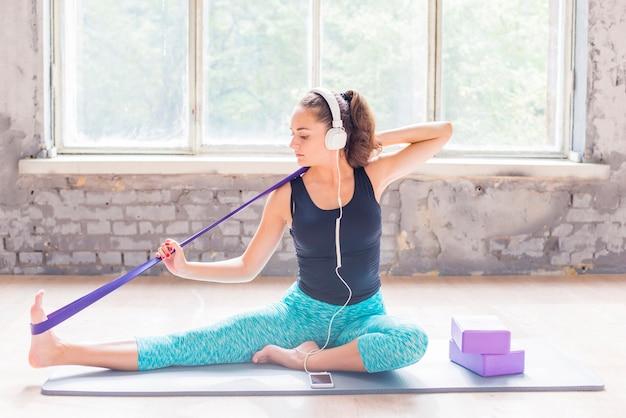Donna che si esercita con la cinghia di yoga sul materassino