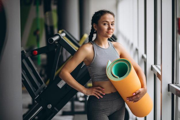 Donna che si esercita in palestra tenendo la stuoia di yoga