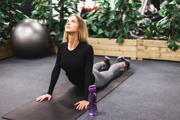 Donna che si estende sul tappeto esercizio in palestra