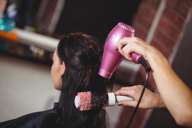 Donna che si fa asciugare i capelli