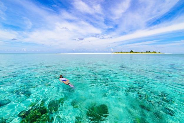 Donna che si immerge sul mare caraibico tropicale della barriera corallina, acqua blu turchese. indonesia wakatobi arcipelago, parco nazionale marino, meta turistica di immersioni subacquee