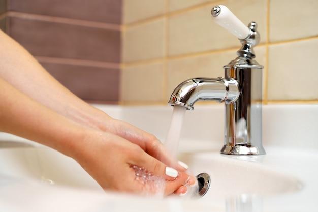 Donna che si lava le mani con la fine del sapone in su