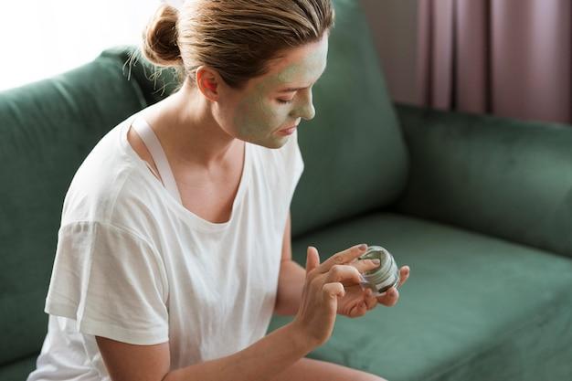 Donna che si prende cura di se stessa con la maschera facciale