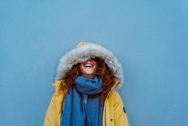 Donna che si protegge con il cappuccio dalle piogge invernali