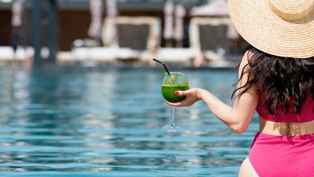 Donna che si rilassa allo stagno con un drink