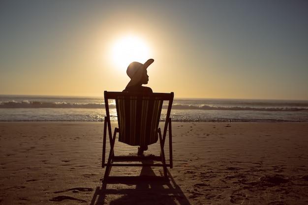 Donna che si rilassa in una sedia di spiaggia sulla spiaggia