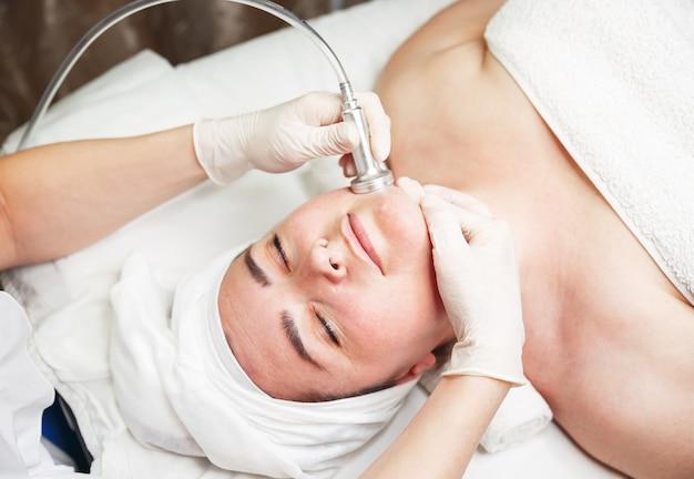 Donna che si rilassa mentre cosmetologo che per mezzo del dispositivo di massaggio sul suo fronte