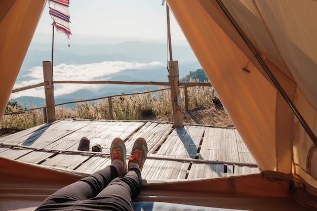 Donna che si rilassa nel campeggio e che guarda in in montagna. concetto di viaggio