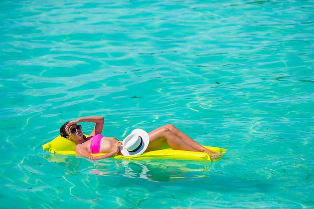 Donna che si rilassa sul materasso di aria gonfiabile all'acqua del turchese