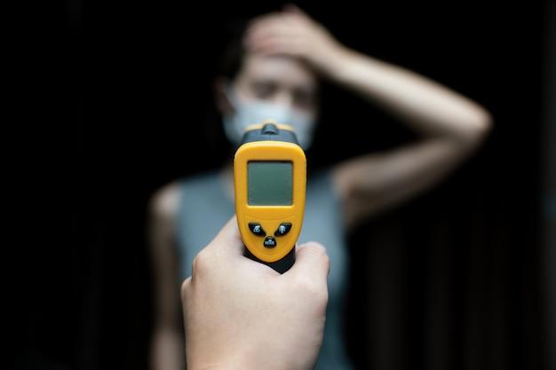Donna che si sente male indossando maschera protettiva. con il controllo manuale della sicurezza alle porte, utilizzare il termometro digitale per controllare la temperatura.