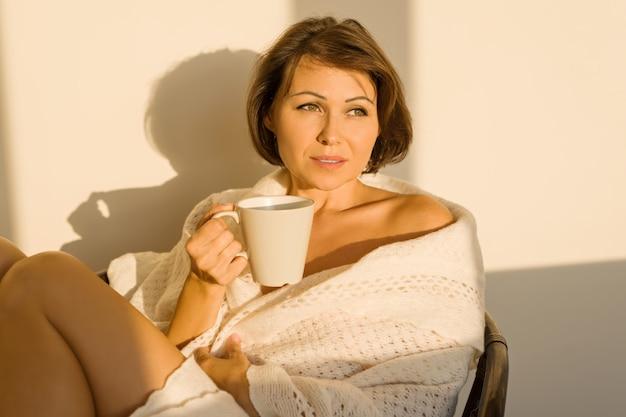 Donna che si siede a casa su una sedia in coperta lavorata a maglia di lana