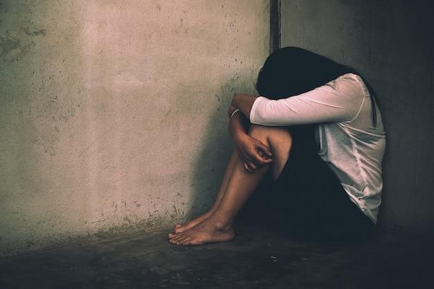 Donna che si siede a fatica, infelice nella stanza, violenza domestica, abuso e persone.