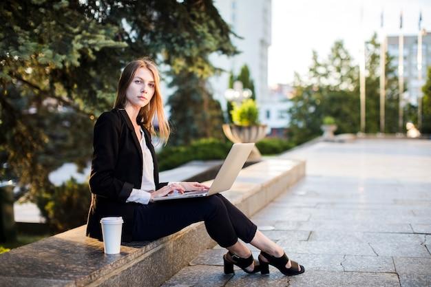Donna che si siede all'aperto con il computer portatile