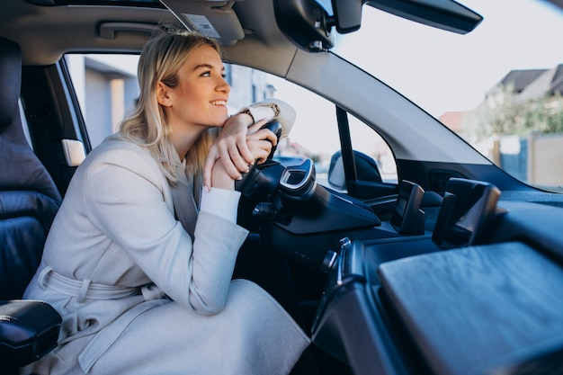 Donna che si siede all'interno dell'elettro automobile mentre si carica
