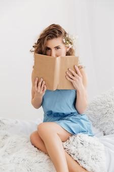 Donna che si siede all'interno sul fronte del copriletto con il libro.