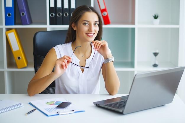 Donna che si siede allo scrittorio, lavorando al computer portatile in ufficio moderno