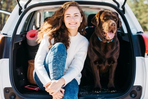 Donna che si siede con il suo cane nel bagagliaio aperto
