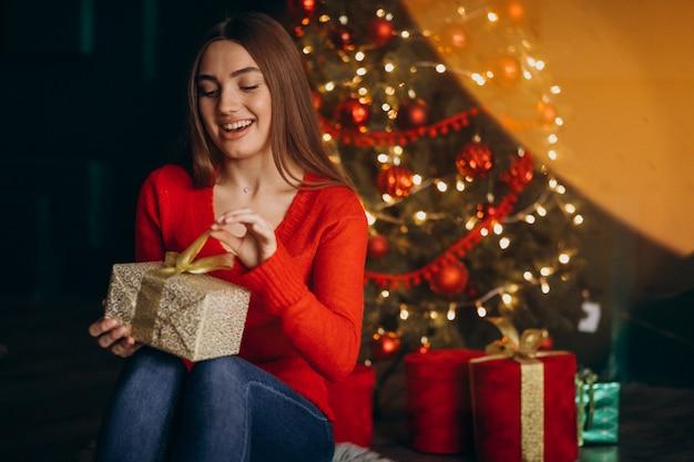 Donna che si siede dall'albero di natale e che disimballa regalo di natale