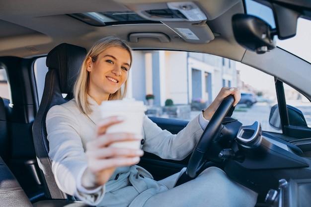 Donna che si siede dentro l'elettro automobile mentre si carica con una tazza di caffè