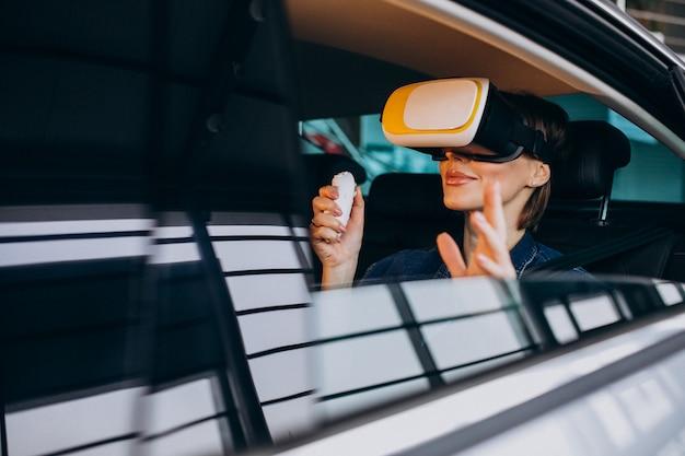 Donna che si siede dentro un'automobile che indossa i vetri del vr