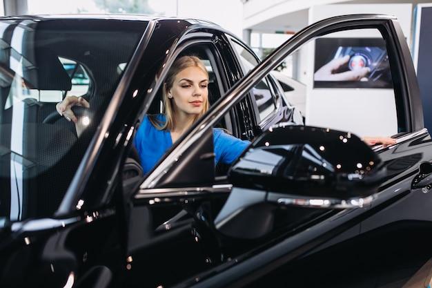 Donna che si siede dentro un'automobile in una sala d'esposizione dell'automobile