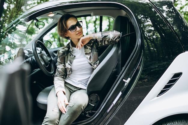 Donna che si siede dentro un'automobile nella foresta