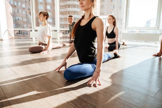 Donna che si siede e che allunga le gambe nel gruppo allo studio di yoga