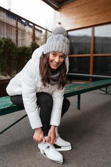 Donna che si siede e che lega i pizzi sulla figura pattina alla pista di pattinaggio