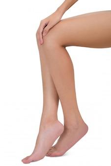 Donna che si siede e che tiene la sua gamba con il massaggio del ginocchio nell'area di dolore isolata su bianco