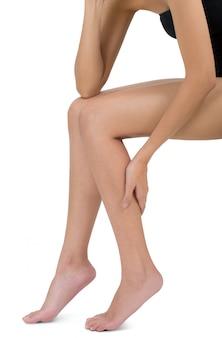 Donna che si siede e che tiene la sua gamba con il massaggio del vitello nell'area di dolore isolata su bianco