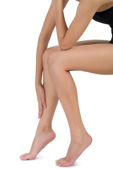 Donna che si siede e che tiene la sua gamba con lo shin di massaggio nell'area di dolore isolata su bianco