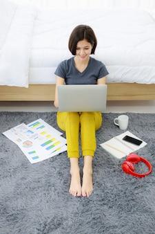 Donna che si siede e che utilizza computer nella camera da letto