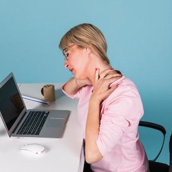Donna che si siede in poltrona soffre di dolore al collo mentre si utilizza il computer portatile