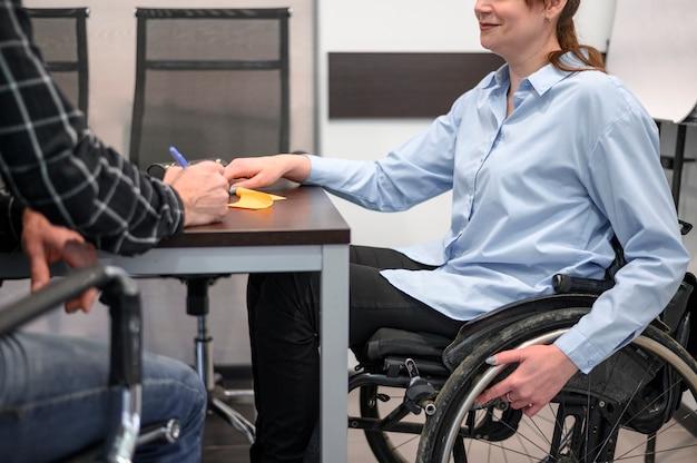 Donna che si siede in sedia a rotelle allo scrittorio