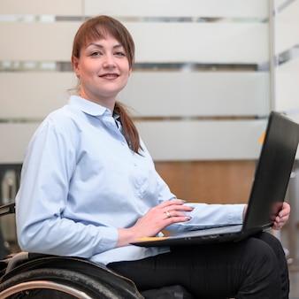 Donna che si siede in sedia a rotelle con il computer portatile