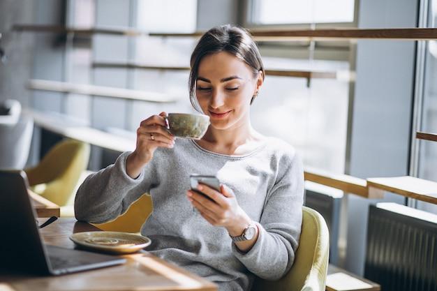 Donna che si siede in un caffè bevendo caffè e lavorando su un computer