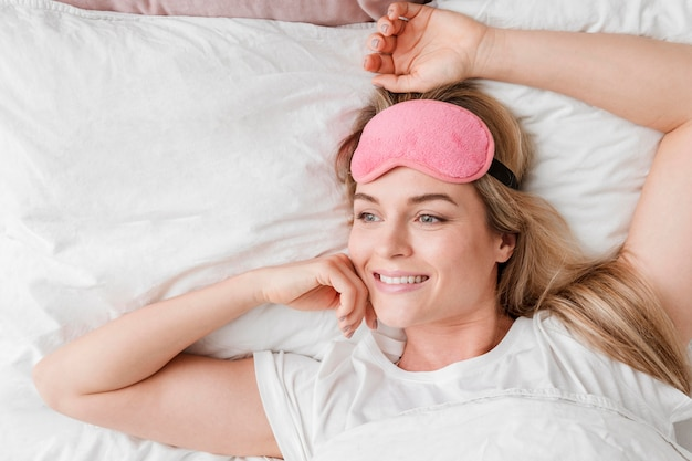 Donna che si siede nel letto con la maschera di sonno