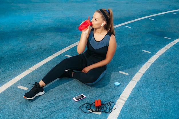 Donna che si siede nel parco giochi con una bottiglia di acqua