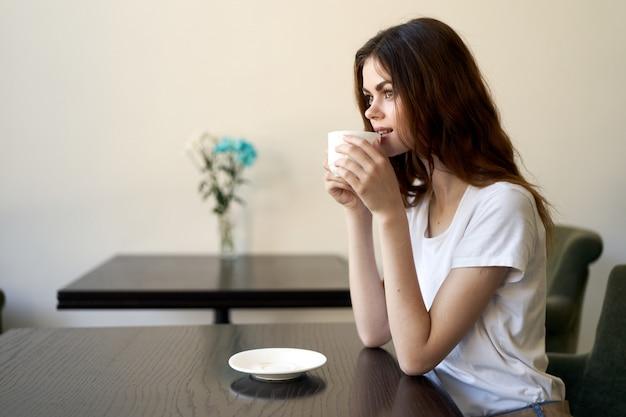 Donna che si siede nella caffetteria, rilassarsi e bere caffè