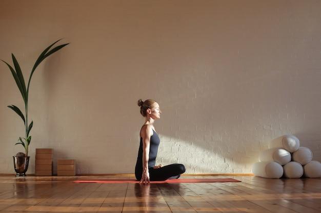 Donna che si siede nella meditazione di posizione di loto