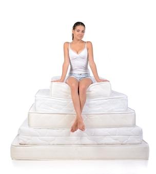 Donna che si siede su molti materassi.